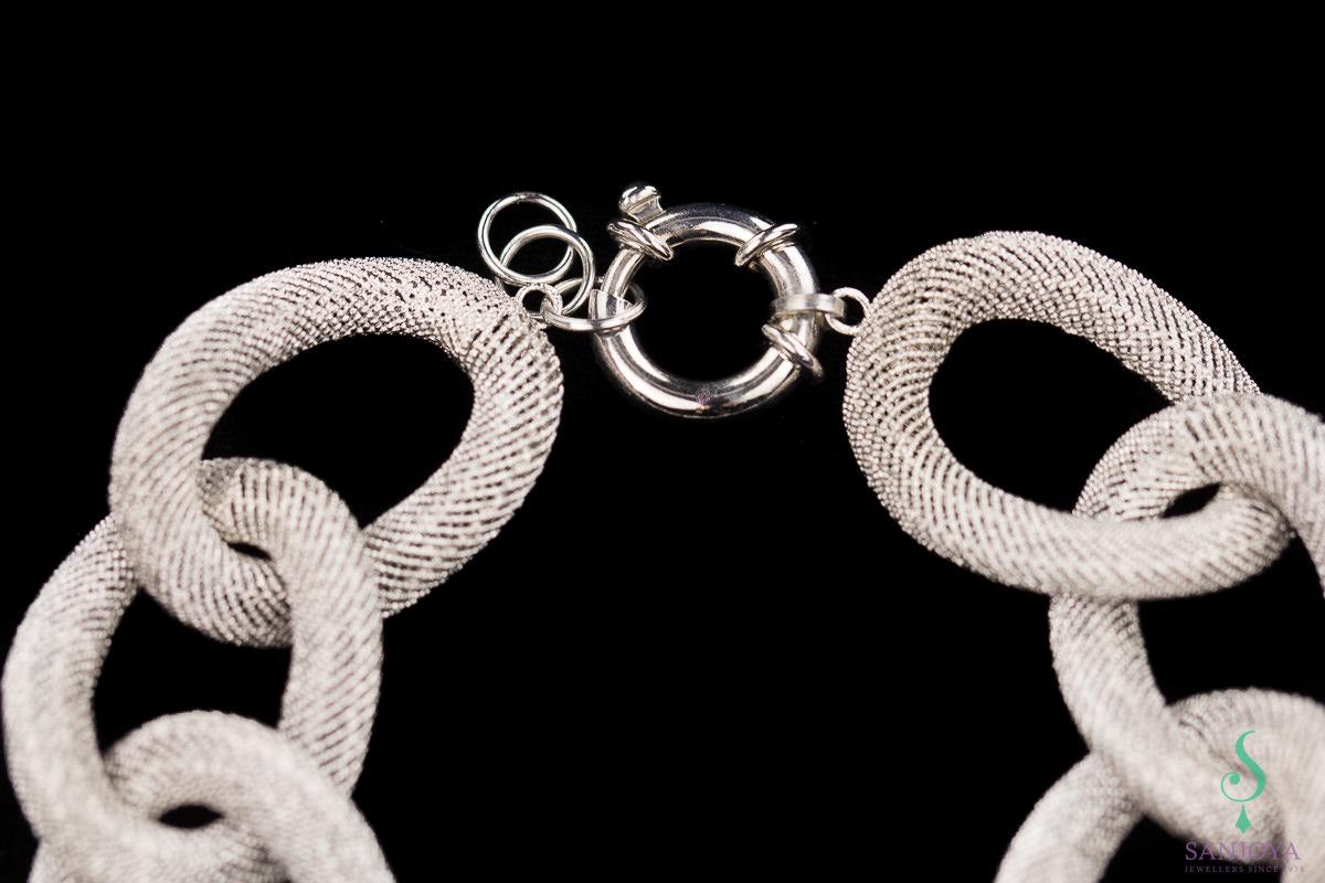 Brede zilveren schakelarmband met fraai transparant patroon